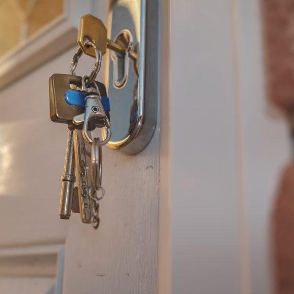 Close up of a house key in the keyhole of a white door with other keys on a ring hanging down