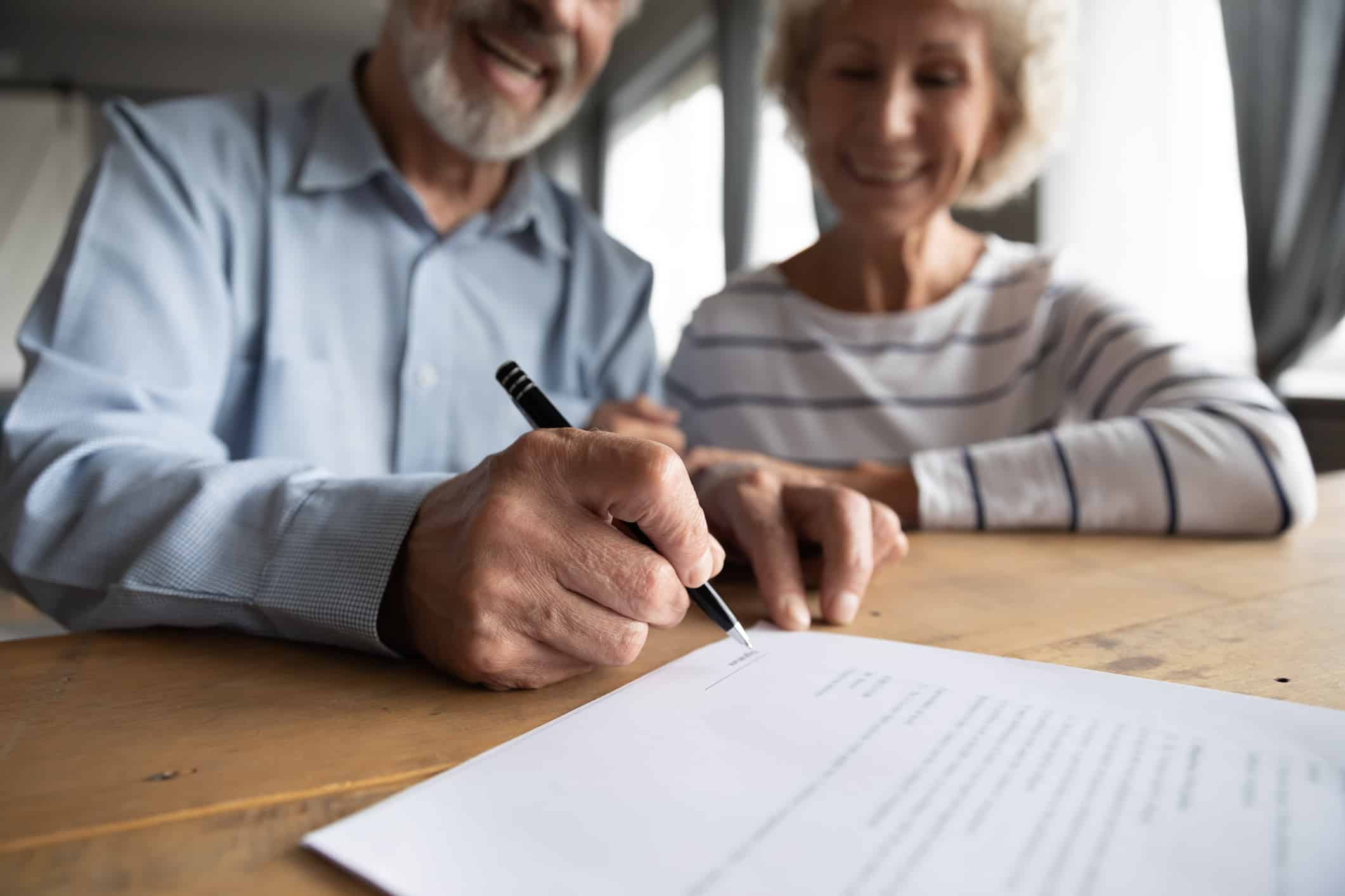 Close up focus on wrinkled male hand signing paper document.