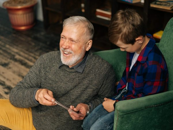 Middle shot portrait of cheerful bearded gray-haired grandfather with his grandson having fun looking at an old photo album, enjoying memories watching family photo album at home in living room