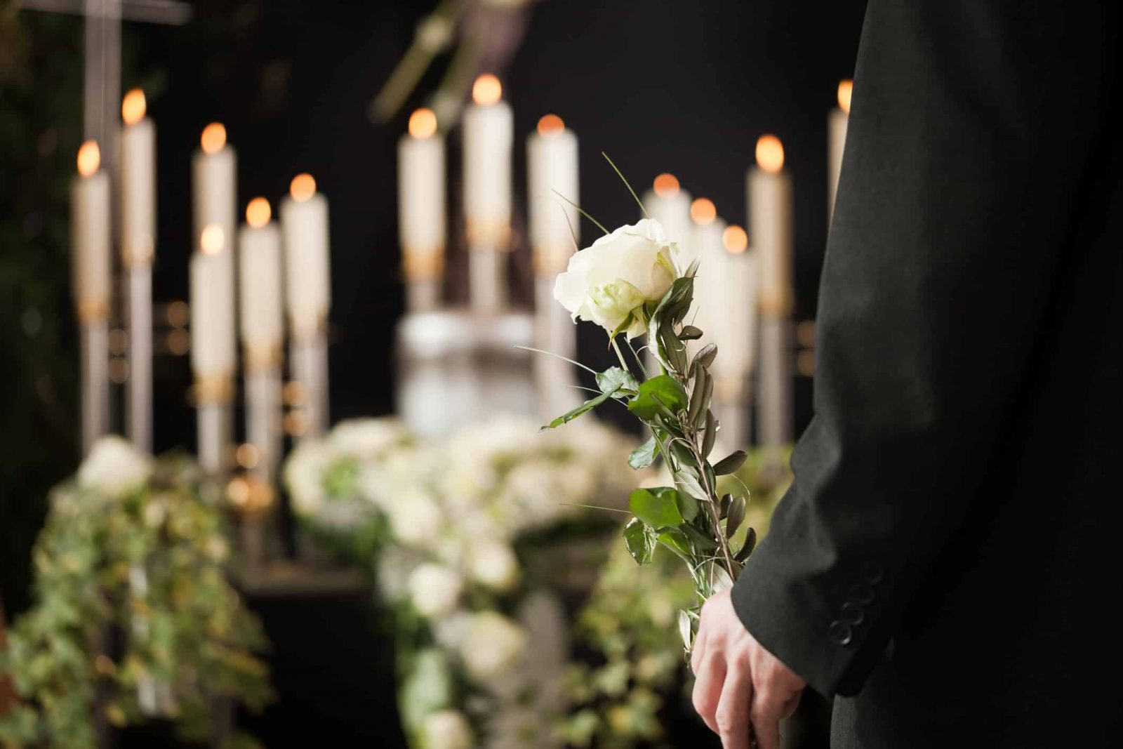Man holding a white rose in front of urn at funeral